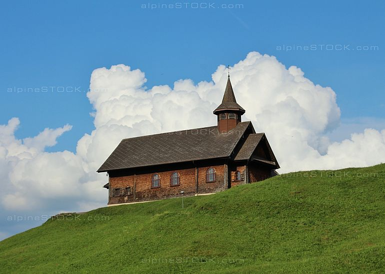 Old tomber chapel on a green hill in Stoos