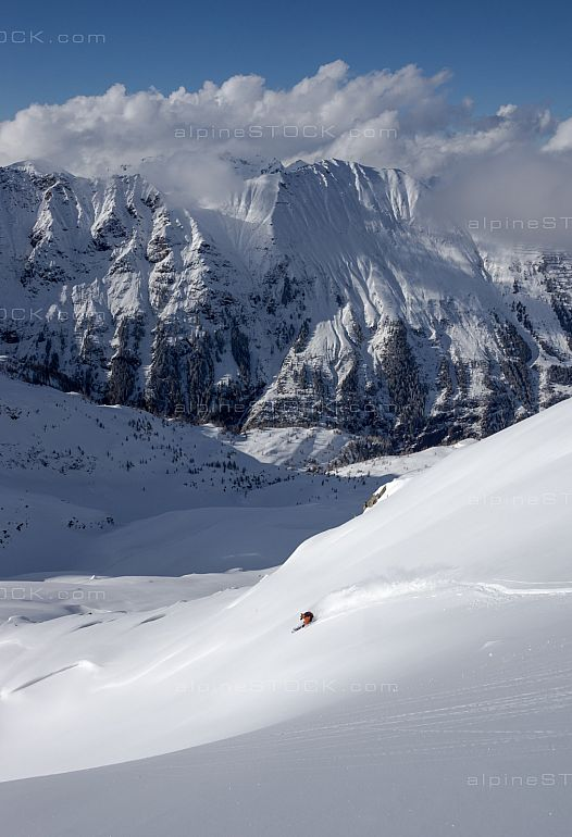 Freeride Skier in deep powder with mountain view