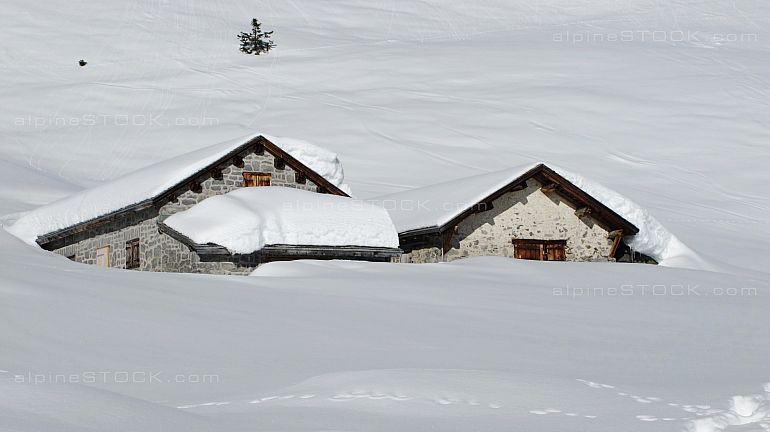 alpine huts covered with snow