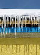 Icicles hanging from a roof with yellow blue paint