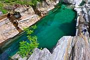 Man looks at green river pond Verzasca Lavertezzo