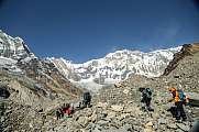 trekker walk to tent peak in abc himalaya over rocks