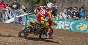 A motocross rider exits a corner at a competition